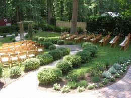 wood chairs set up in backyard for wedding ceremony around pergola and pathway backyard wedding ideas