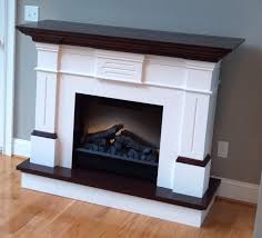 interior white fireplace mantel with black woden top connected by grey wall and laminate flooring