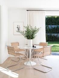 tulip table paired with beachy woven chairs for a modern earthy dining room on simple white