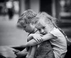 Little sad girl with boy using ...