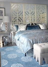 Glam bedroom with gray blue walls paint color, mirrored console table  nightstands with gold trim