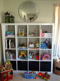 white ikea toy storage filled with books and doll and other goods with  round mirror above