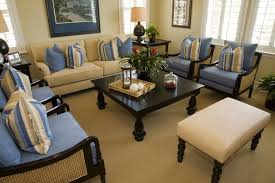 a small nautical themed living room in light blue and beige with two end tables decorating without lamps l0