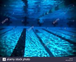 swimmer reaches opposite end of a 25 meter outdoor swimming pool in a flash of white