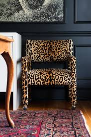 dark walled dining room with leopard chairs and a vine oriental