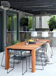 teak outdoor dining table with black metal dining chairs under black pergola