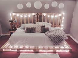 use some old pallets and add lights to make your own bed frame handmade