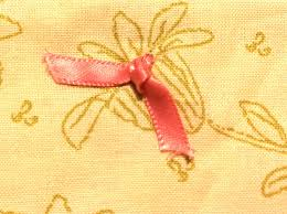 Knots Used In Quilting, Techniques and Tips for Tying Quilts & Quilting knot tied with pink ribbon Adamdwight.com