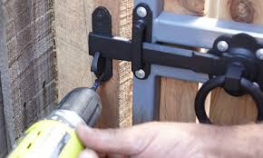 man installing gate catch plate