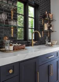 masculine furniture. navy kitchen cabinets with brass handles and details white stone countertops masculine furniture