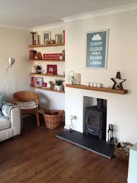 eclectic living room with oak floating shelves and log burner nice and cosy