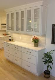 Painted White cabinets in built in storage hutch with reduced depth cabinets  in base