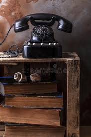 dusty vine bakelite phone on a wooden fruit box with old book stock image