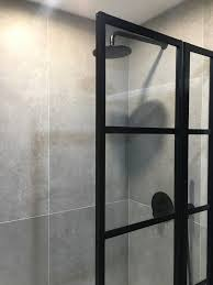 Overbath shower screen in a black grid style installed in this ...
