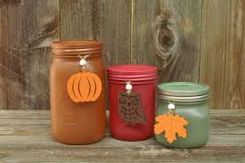 we sprayed mason jars with krylon amber ruby and seafoam spray paint to create this display tie wooden fall cut outs to the jars for an added touch