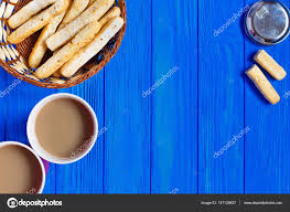 two cups of cappuccino and italian bread sticks served in rustic basket on blue wooden table copy space breakfast in cafe photo by jetsamui gmail com