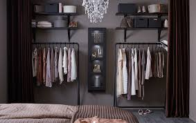 An open wardrobe consisting of hanging racks, open shelves and a display  cabinet, filled