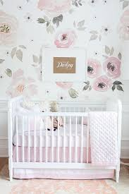 white crib with pink olio crib bedding and beige and pink rug