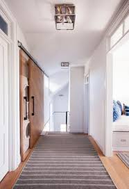 a cottage hallway is filled with a sliding door on rails which opens to a small laundry room filled with a stacked washer and dryer alongside a gray striped