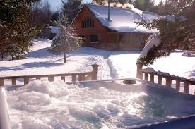large snow covered cabin with steaming bubbling hot tub
