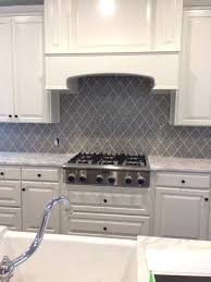 white gray backsplash white cabinets and beautiful stone counters in this kitchen are the perfect companions