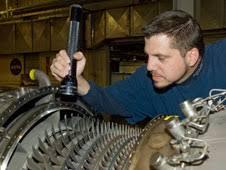 jet engine mechanic aaron rumsey inspects compressor blades on a ge f 404 engine turbine engine mechanic