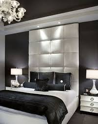 Contemporary bedroom with black walls and white bed frame and tufted  headboard