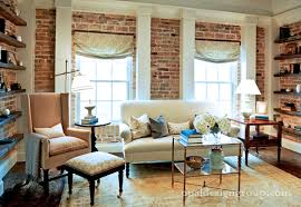 Chic living room with exposed brick walls, white sofa,light brown velvet  wingback chair with black ottoman, brass coffee table and espresso stained  floating ...