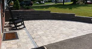 Paver patio with slit drain system and retaining wall