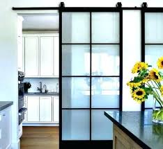 a set of sliding barn doors with glass panels serves separates spaces while providing light to sliding door panels