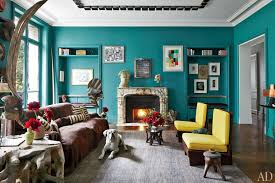 bright teal walls a marble fireplace grey area rug and yellow armless chairs