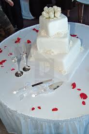 A White 3 Tier Square Wedding Cake With Icing Decorations Is
