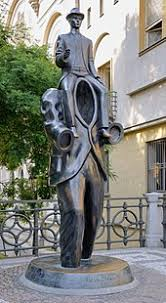 franz kafka  the statue is a man no head or arms another man sitting on