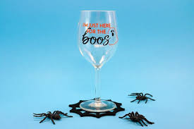wine glass with vinyl and spiderweb coaster with fake spiders