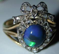 ring with a black opal diamonds in a heart and bow motif set in 18k gold for