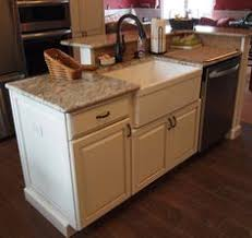 Charming Kitchen Island With Farm Sink And Dishwasher And Elevated Breakfast Bar.