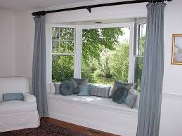 Bay Window Seat with Pillows- like the curtain idea. I wonder how much it  would cost to build in a bay window to the front?