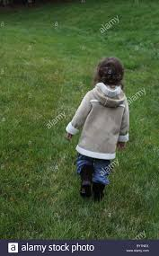 tall green grass field. A Small Child Walking In Field Of Tall Green Grass