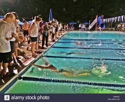 end of a heat at an evening swim meet stock image