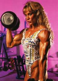 corinna everson lifting weights in the gym displaying her muscular arms