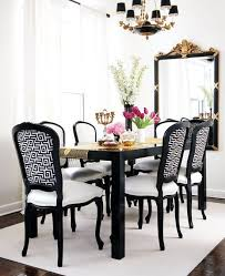 glamorous dining room with glossy black dining table black french chairs upholstered in white black greek key fabric with white leather cushions