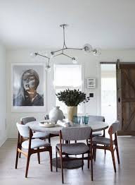 modern dining room with round dining table gray upholstered dining chairs and a modern globe light fixture