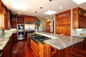 kitchen centered around lengthy island featuring full range sink and dishwasher plus raised