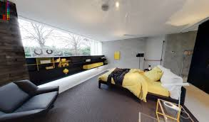 yellow and gray bedroom: yellow and grey bedroom with fitted storage and black leather armchair