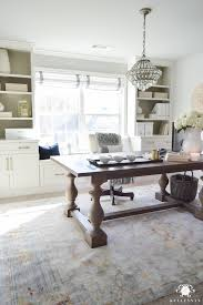 crystal chandelier over table desk in office in front of windows and dining room table desk