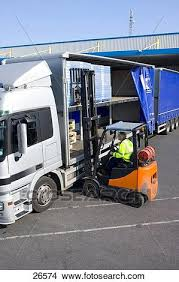 Stock Photo Of Worker Driving Forklift Loading Inventory On Semi