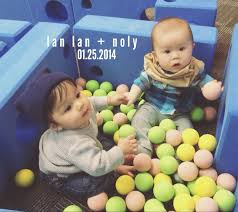 baby boys playing together in ball pit