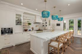 coastal light fixtures wooden chairs white island white cabinets built in kitchen appliances range hood stovetop