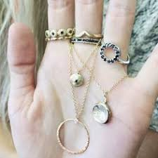 a handful of black diamond and yellow gold jewelry by local austin texas designer