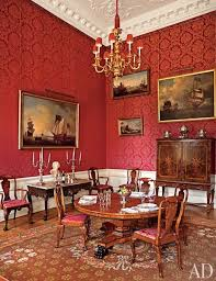 the red dining room features a regency pedestal table surrounded by circa 1860 chairs in the queen anne style archdigest